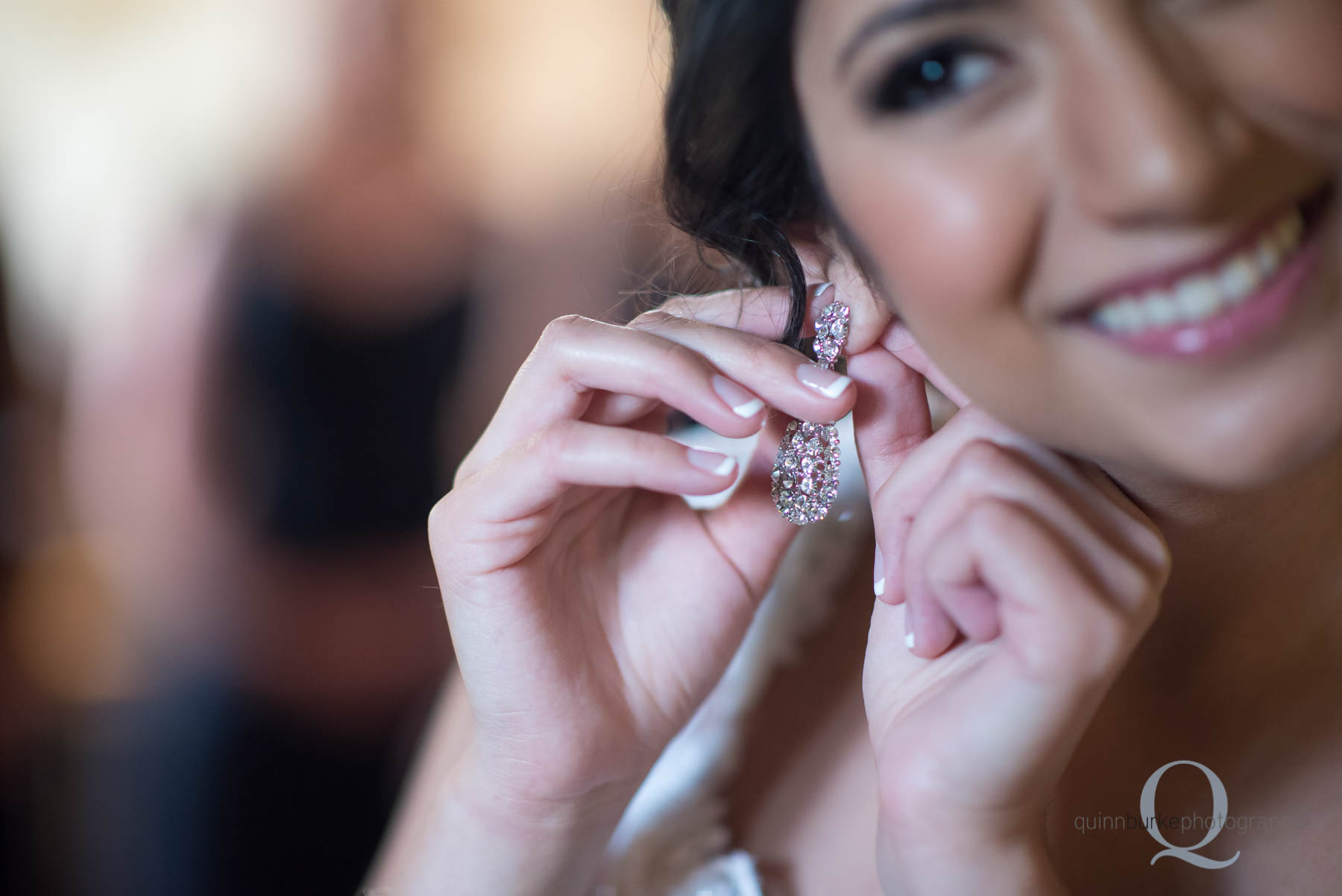 bride putting on earrings at Green Villa Barn