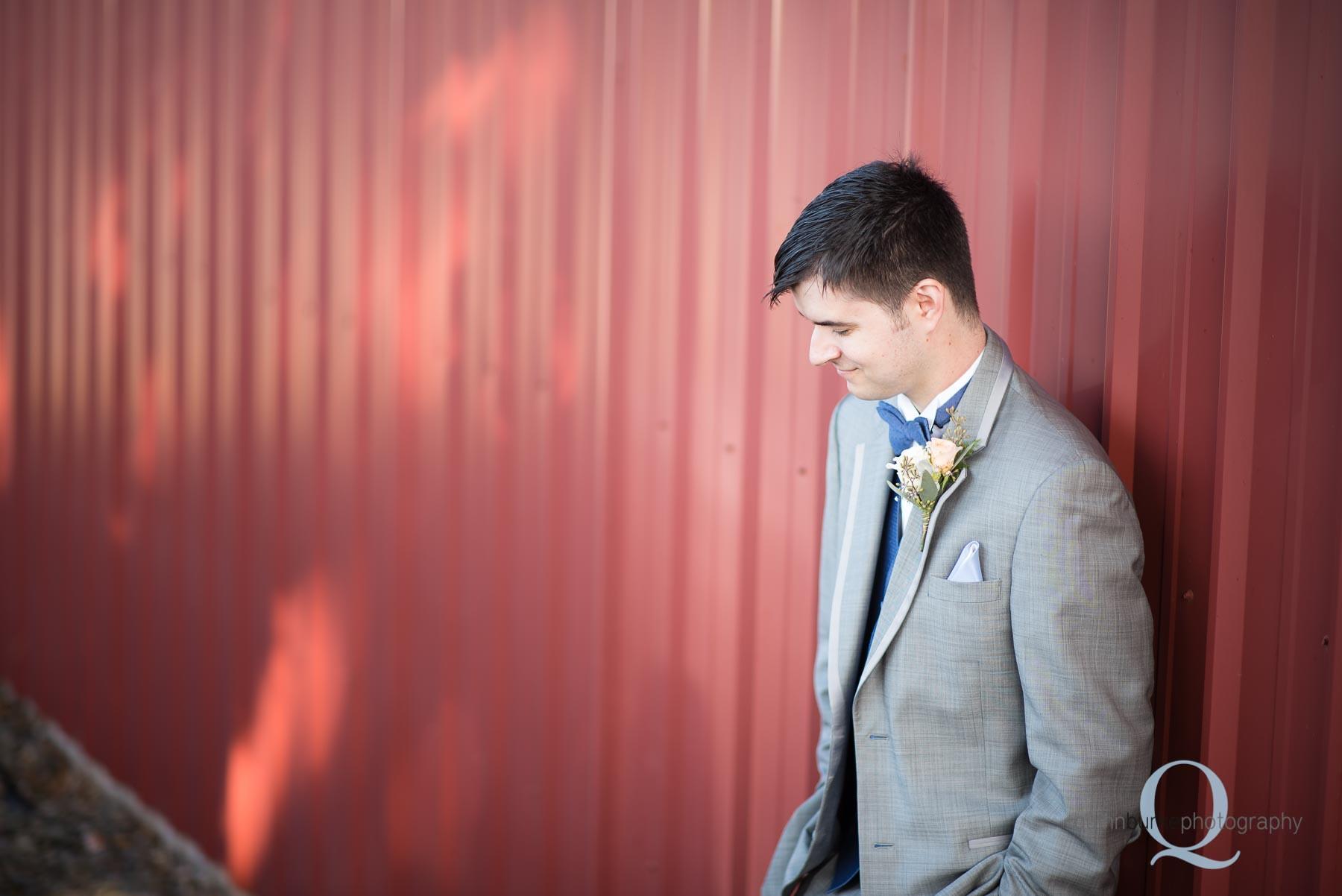 groom against barn before wedding at Perryhill Farm