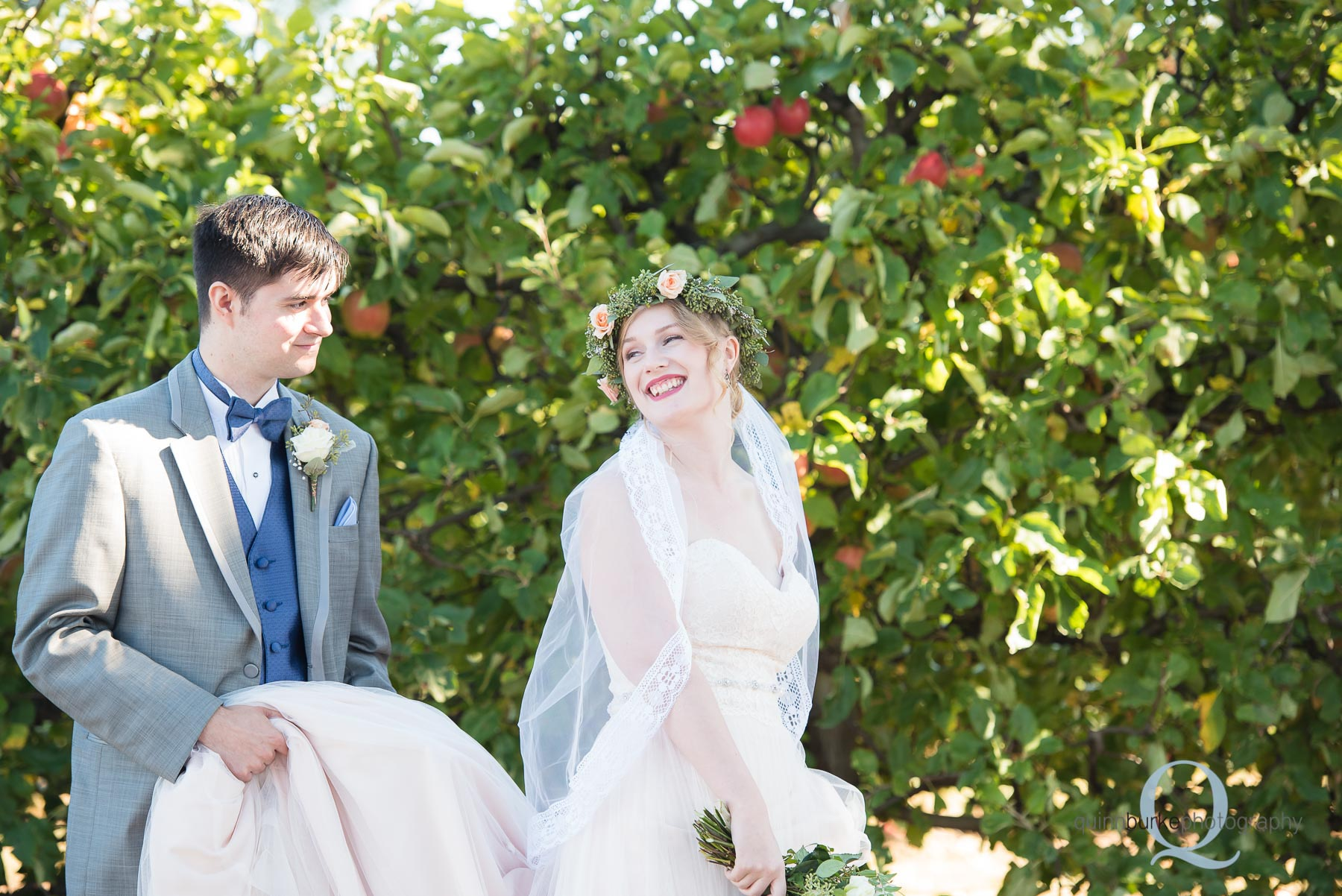 groom carrying bride dress train in orchard Perryhill Farm