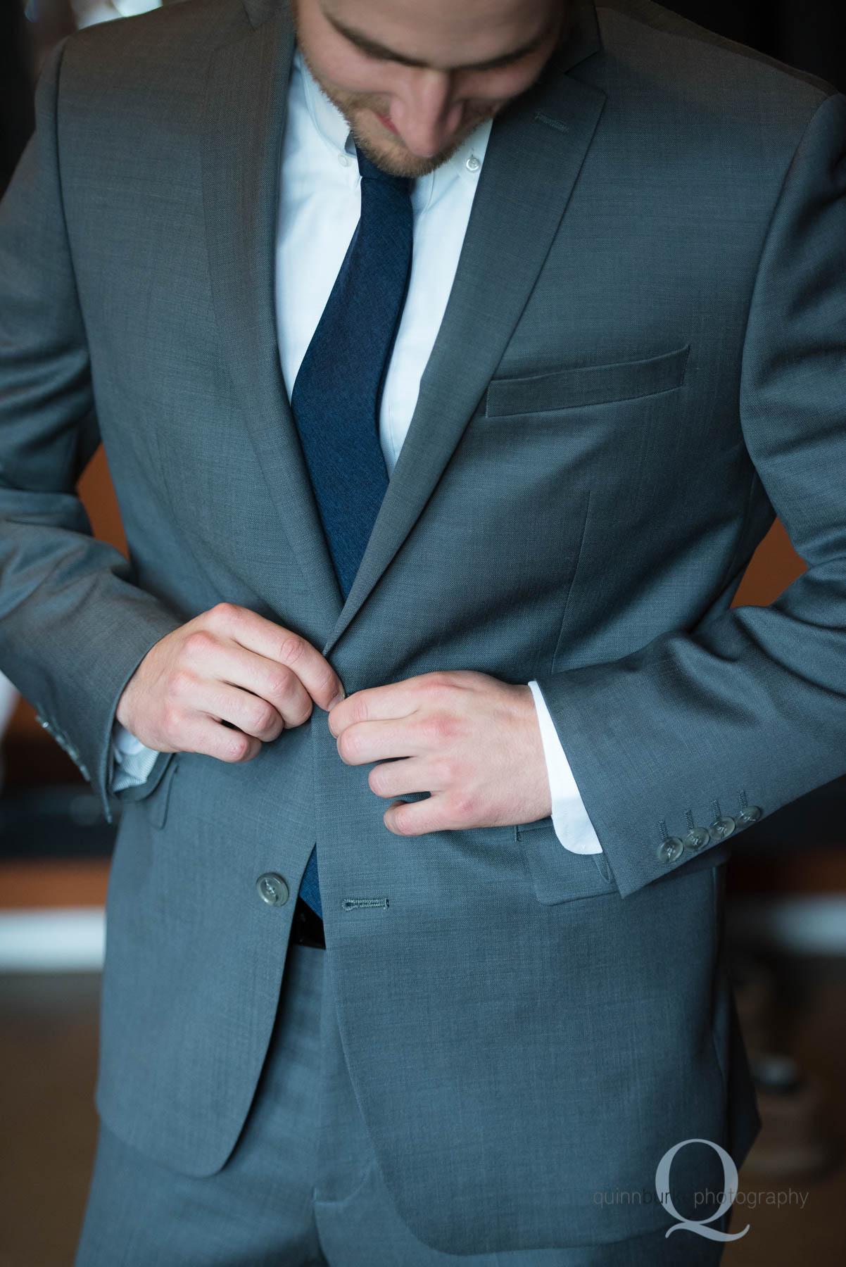 groom buttoning jacket for Green Villa Barn wedding