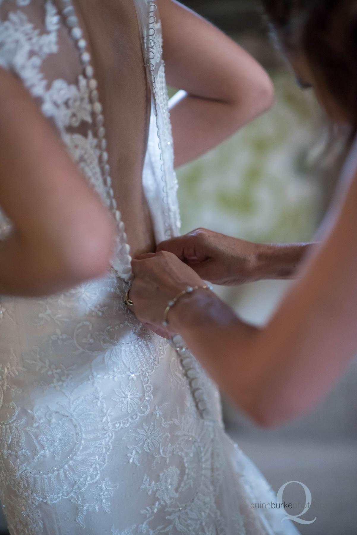 buttoning bride's dress before wedding at Green Villa Barn