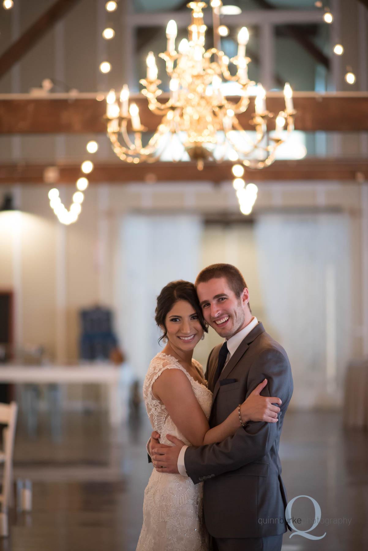 bride and groom under chandelier at Green Villa Barn