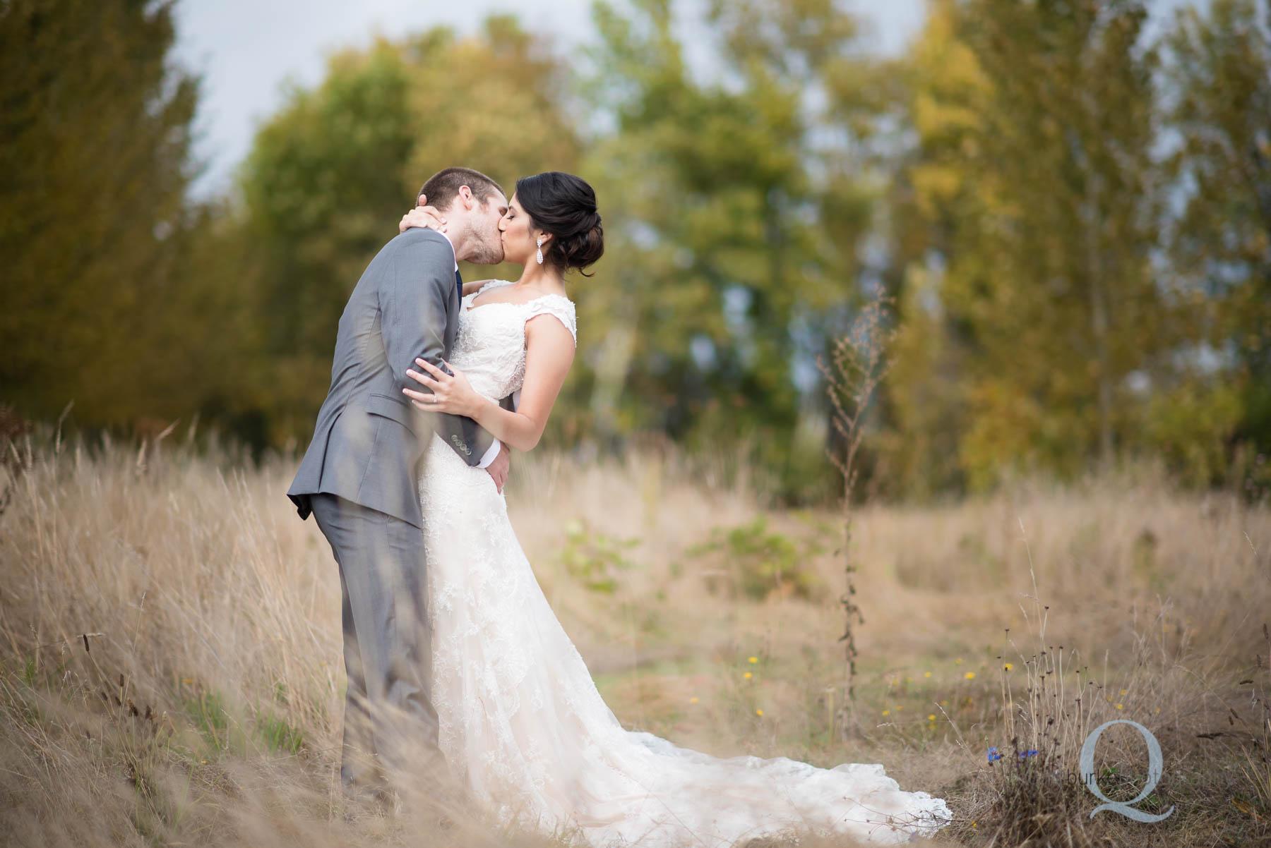 groom kissing bride at Green Villa Barn wedding