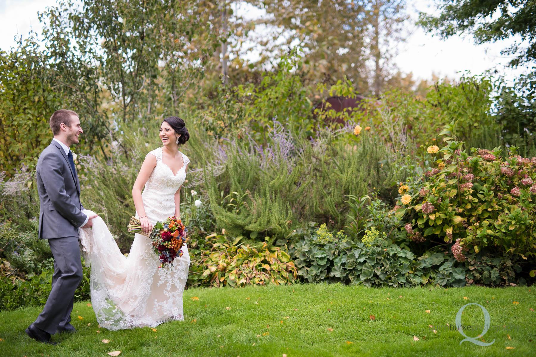 groom helping bride with dress in garden at Green Villa Barn