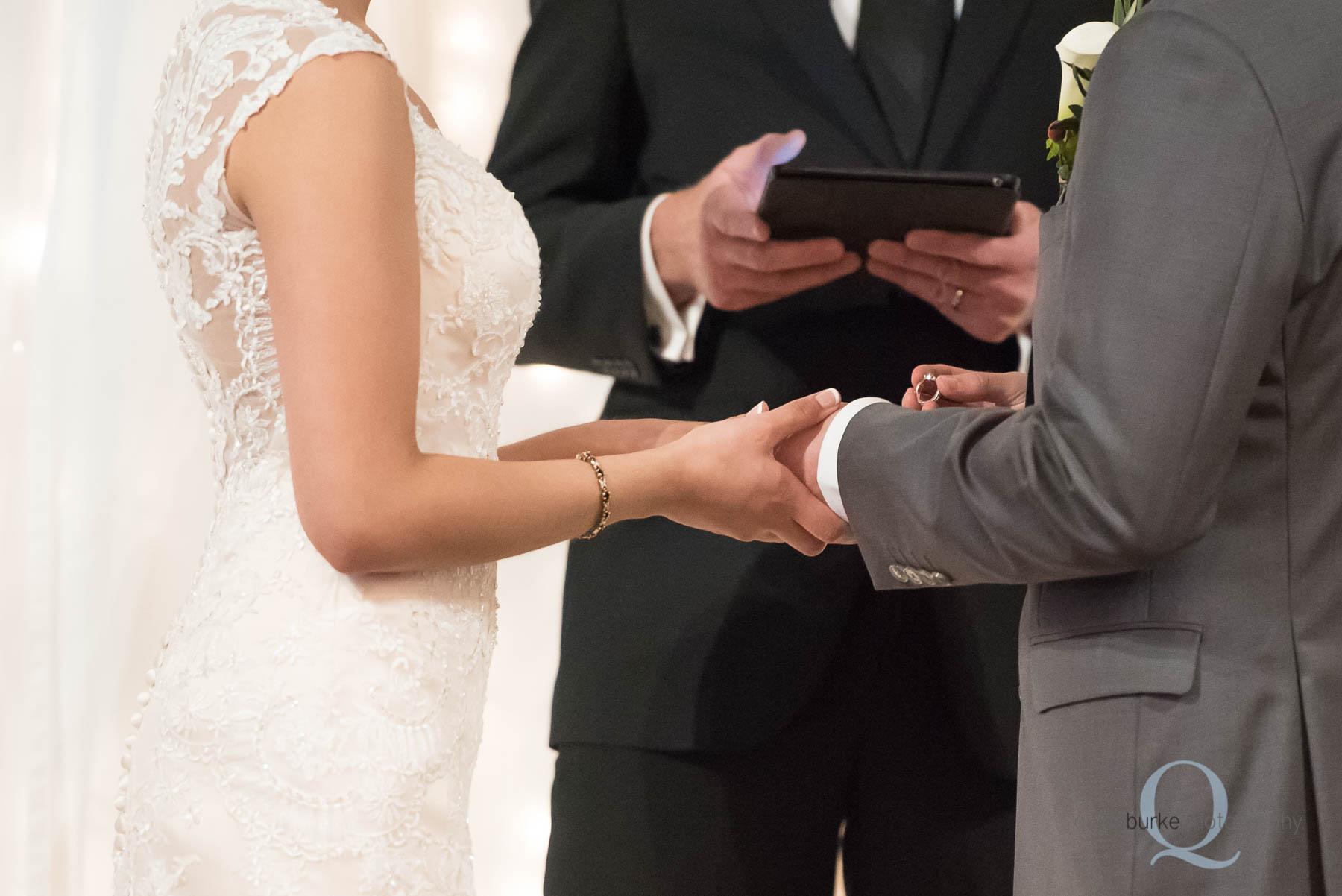 groom placing ring on brides finger Green Villa Barn