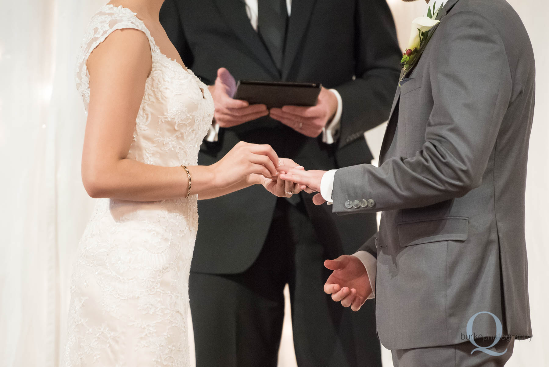bride placing ring on grooms finger wedding ceremony Green Villa Barn