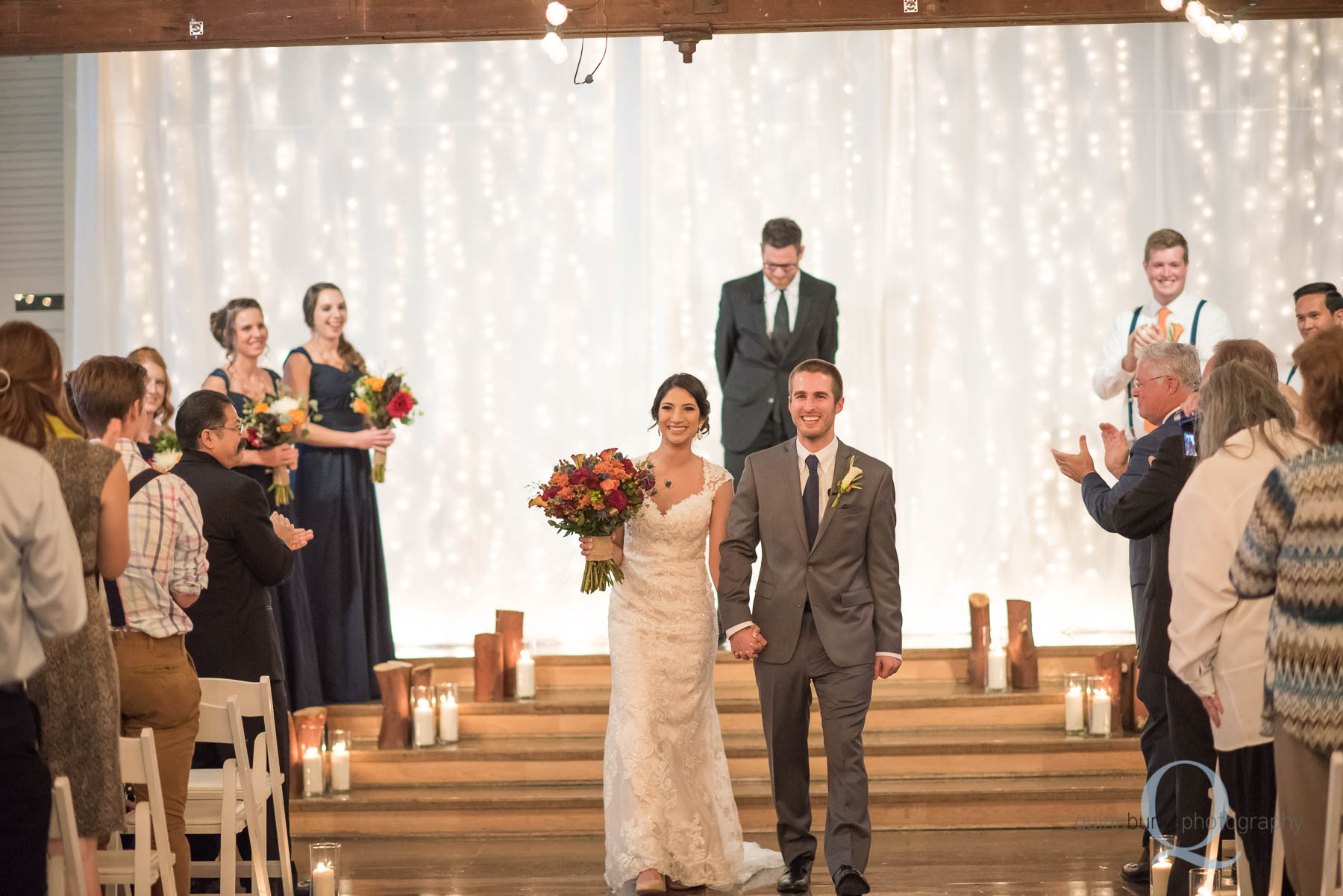 bride and groom walk down aisle Green Villa Barn