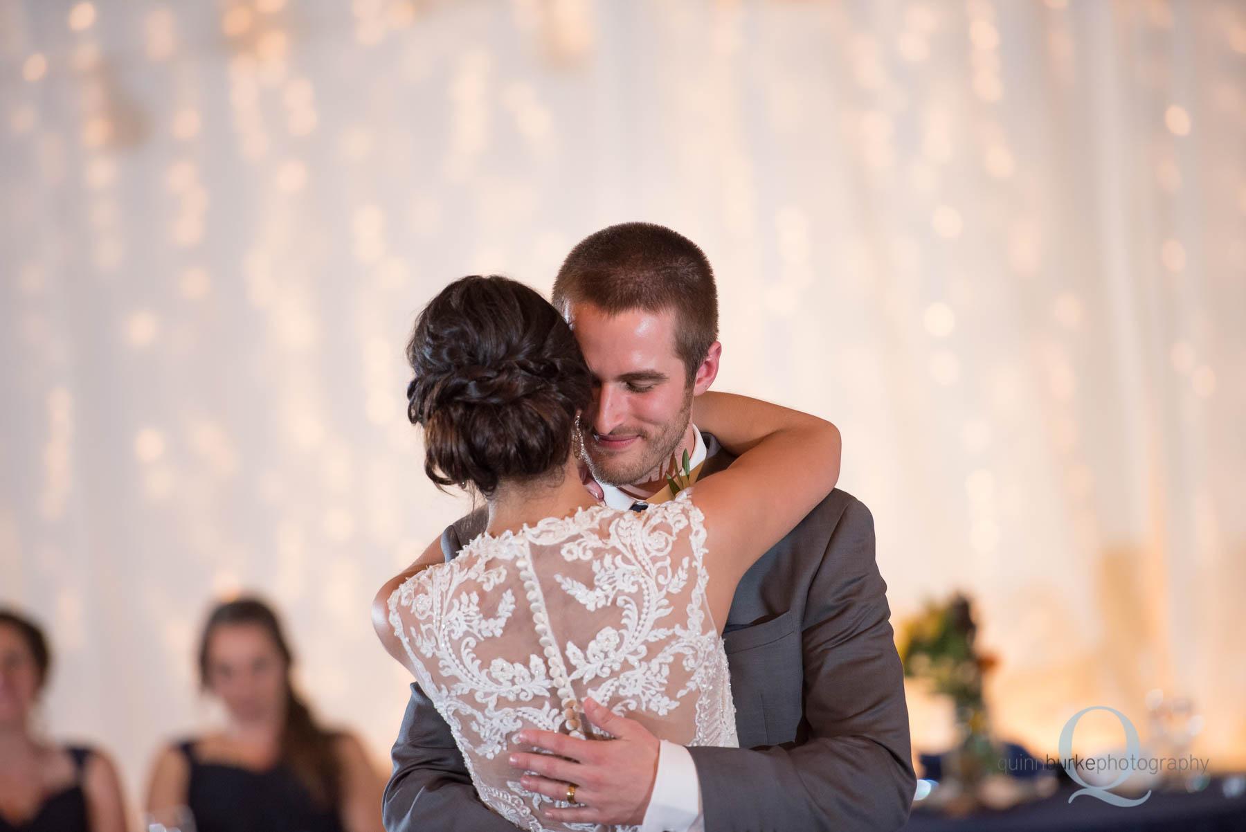 groom hugs bride during first dance at Green Villa Barn