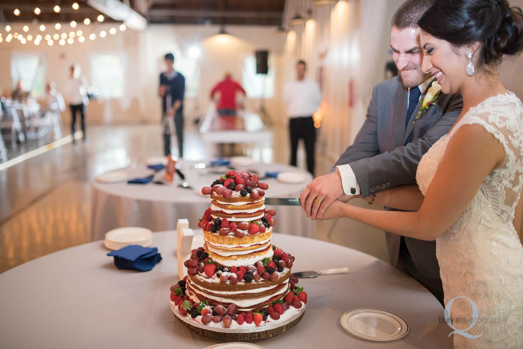 cutting wedding cake at Green Villa Barn