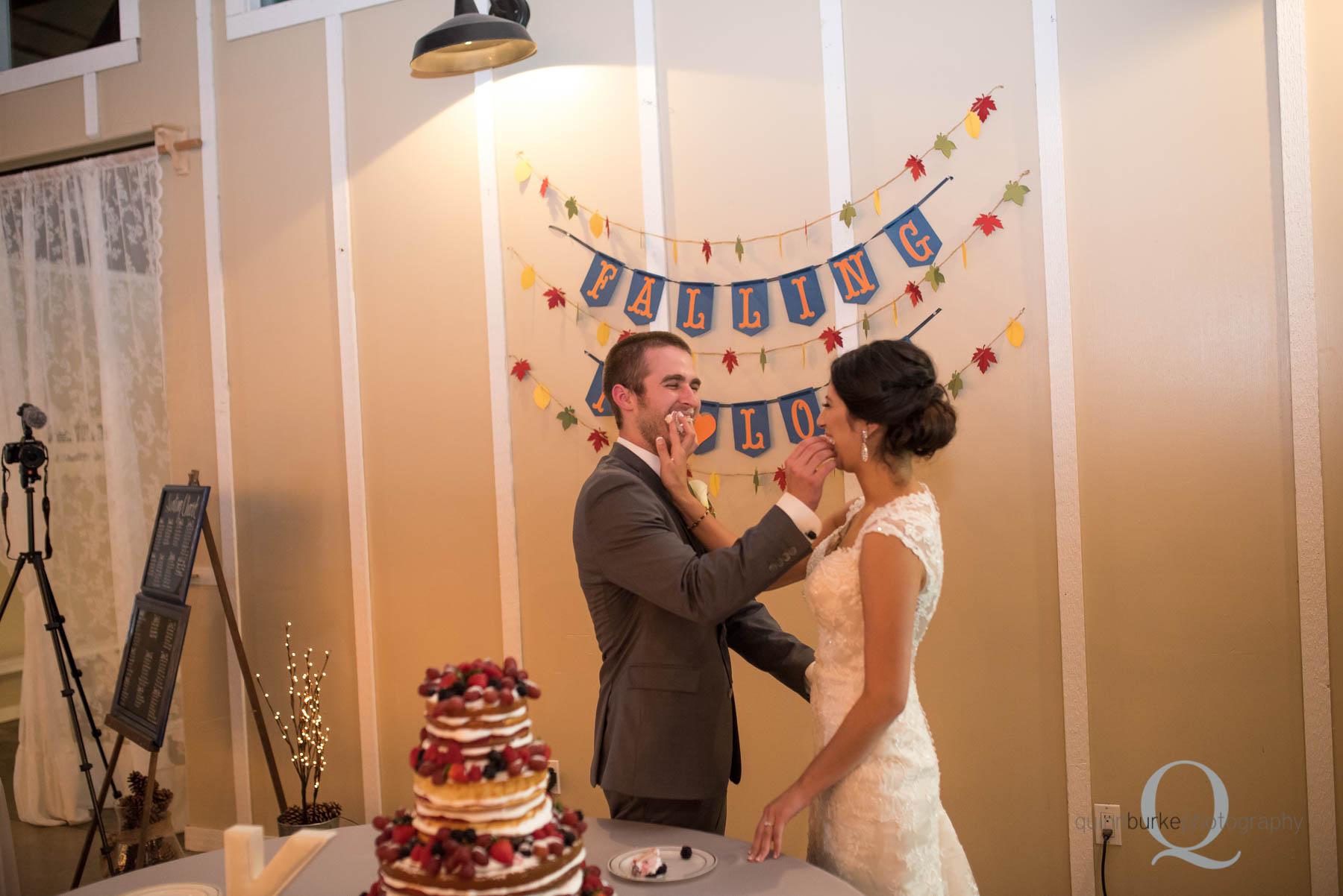 bride and groom feed cake Green Villa Barn wedding