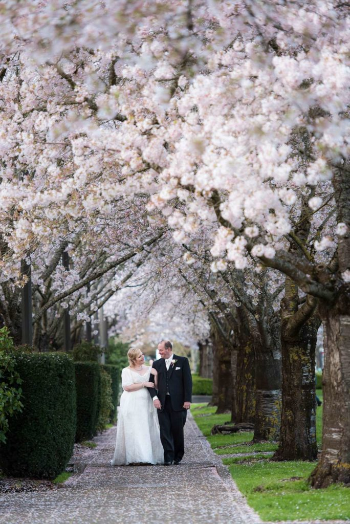 bride groom walking in park cherry blossoms salem oregon wedding