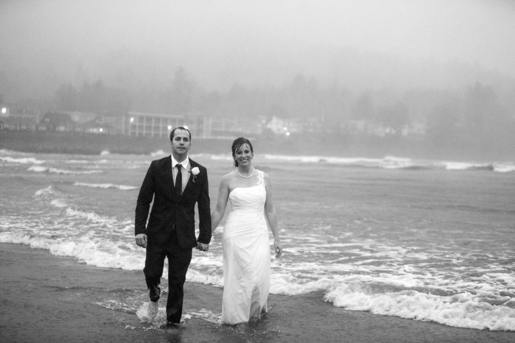 bride groom walking in rain on beach black white seaside oregon wedding