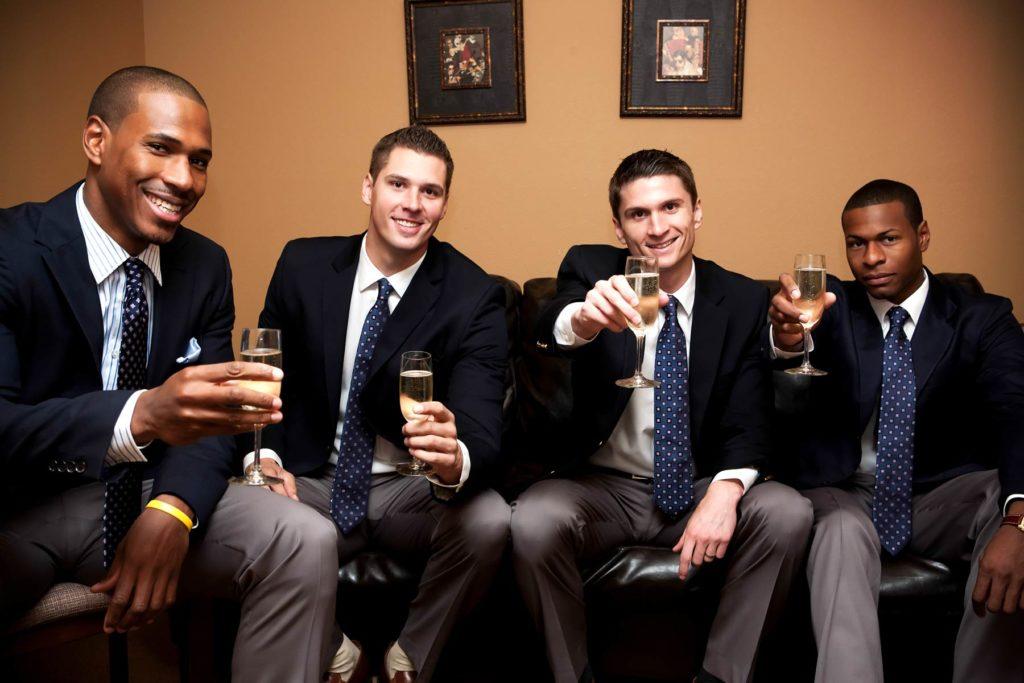 groom groomsmen toasting at wedding